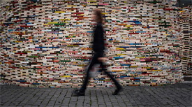 Person walking in front of a mosaic wall