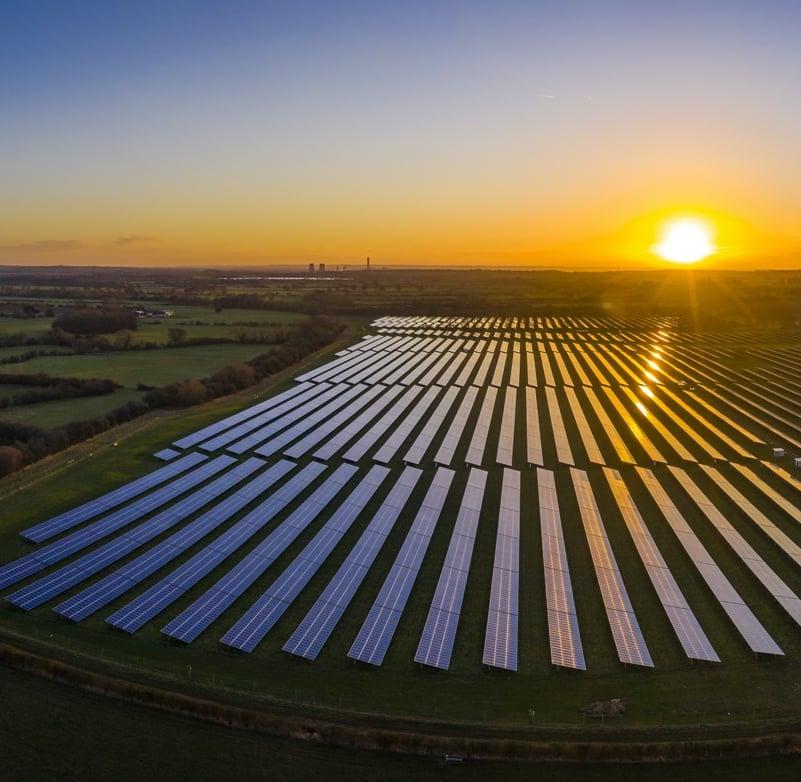 Aerial photo of the sun rising over a solar farm