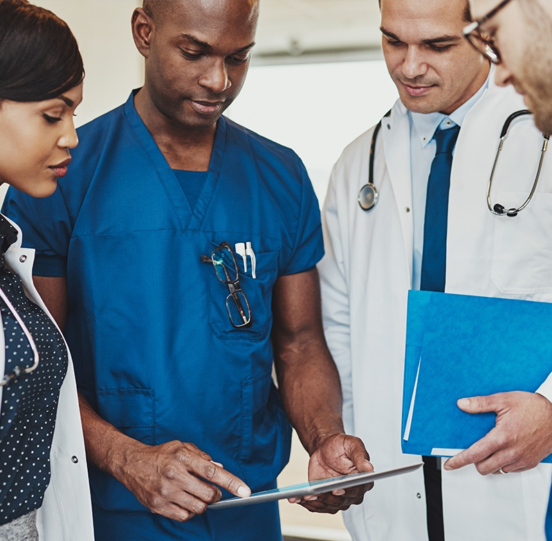 Photo of healthcare professionals reviewing a chart on a tablet