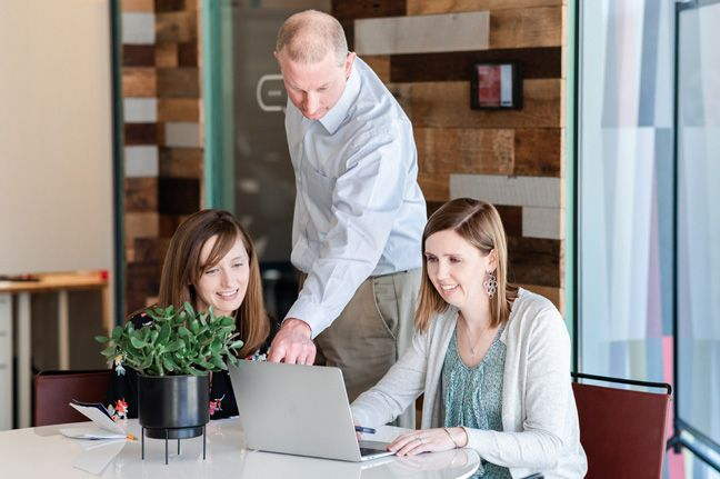 Rick Whittington shows two inbound marketing account managers something on a computer screen